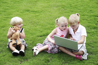 Children with laptop and toy bear