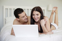 Couple lying forward on the bed using laptop