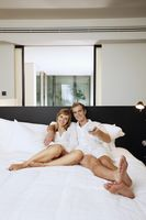 Couple relaxing while watching tv in resort bedroom