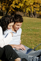 Couple sharing laptop in the park