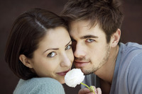 Couple smiling at the camera while holding a white rose