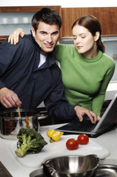 Couple using laptop while cooking in the kitchen