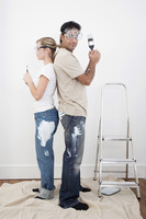 Couple with protection goggles posing with paint brush