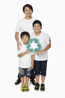 Family of three smiling and holding up a recycle logo