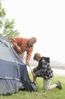 Father and son pitch a tent