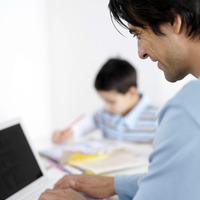 Father using laptop with son doing homework in the background