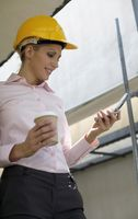 Female architect holding a cup of coffee while text messaging on the phone