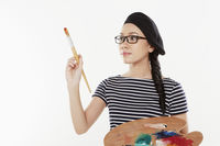 Female artist holding a paint brush and palette