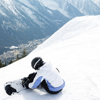 Female snowboarder strapping board onto feet