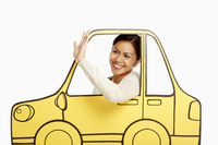 Friendly woman waving from inside a cardboard car