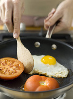 Frying egg and tomatoes