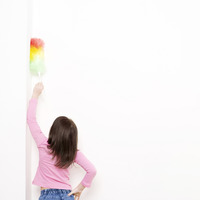 Girl dusting the wall with a feather duster