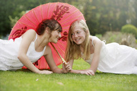Girl lying on the grass sharing an umbrella