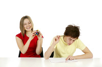 Girl playing with cube while boy is doing homework