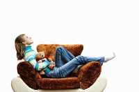 Girl sitting on the couch hugging her teddy bear