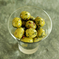 Glass of fresh italian olives on a slate