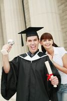 Graduate with trophy and scroll posing with woman