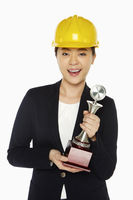 Happy female architect holding up a trophy