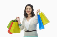 Happy woman holding up colorful paper bags