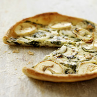 Italian goat cheese and spinach quiche with slice missing