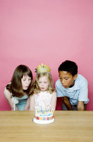 Kids blowing the candles on the birthday cake