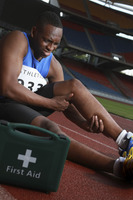 Male athlete lying on track, clasping leg in pain