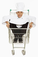 Male chef sitting inside a shopping cart