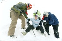 Male skiers helping female skier