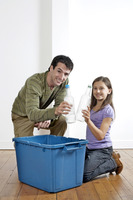 Man and girl holding up plastic bottles to be recycled