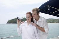 Man and woman filming the sea view from speedboat