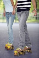 Man and woman holding hands while roller skating