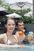 Man and woman sitting in the pool with their drinks