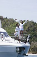 Man and woman standing at the tip of yacht, woman with arms raised