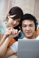 Man and woman using laptop, man with headphones