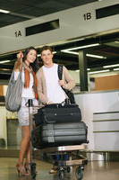 Man and woman with luggage cart upon arrival at the airport