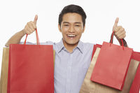 Man carrying shopping bags and showing hand gesture