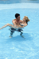 Man carrying woman in pool