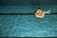 Man carrying woman in swimming pool