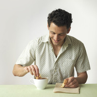Man dipping croissant into a cup of coffee