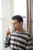 Man drinking coffee while enjoying the view from the window