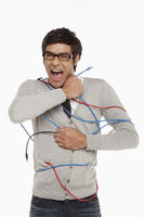 Man freeing himself from tangled network cables