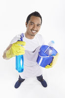 Man holding a variety of cleaning supplies
