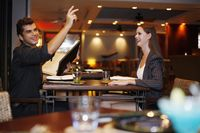 Man holding menu and raising his hand, woman watching man