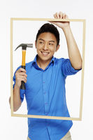 Man holding up a hammer and a picture frame