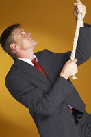 Man in business suit trying to climb up a rope