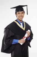 Man in graduation robe holding his diploma scroll
