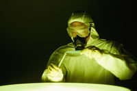 Man in protective suit mixing chemicals