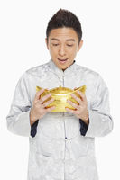 Man in traditional clothing holding a gold ingot