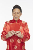 Man in traditional clothing holding up red packets