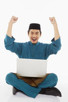 Man in traditional clothing using laptop and cheering